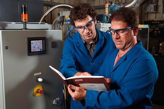 Two men in lab coats and safety glasses reviewing lab notebook