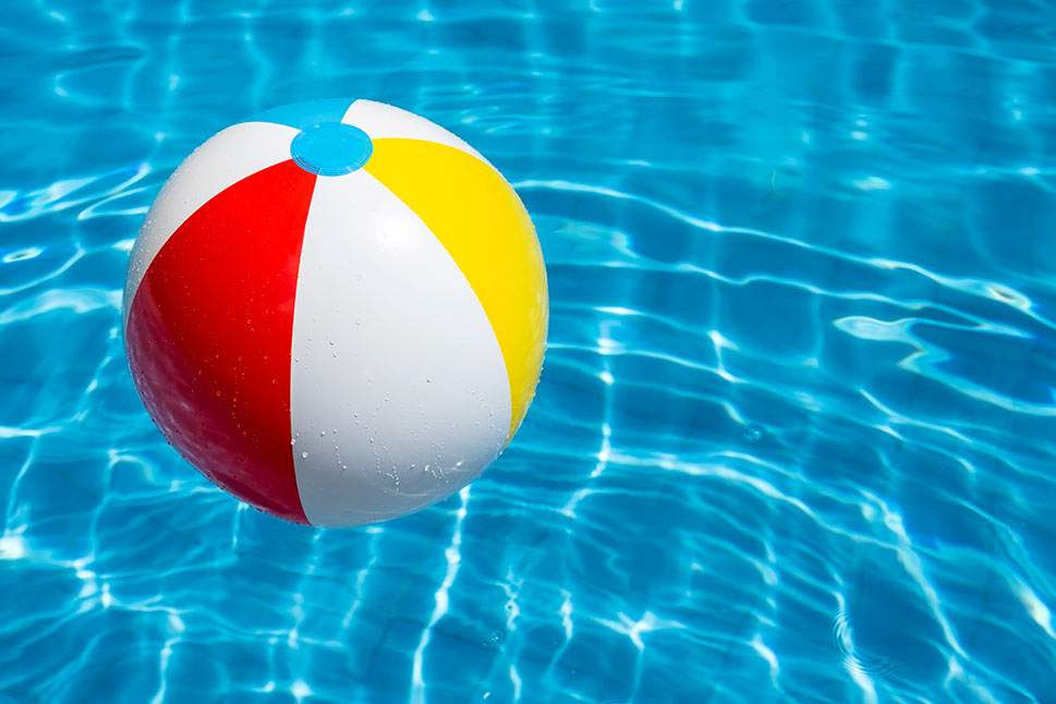 A beach ball floating in a blue pool